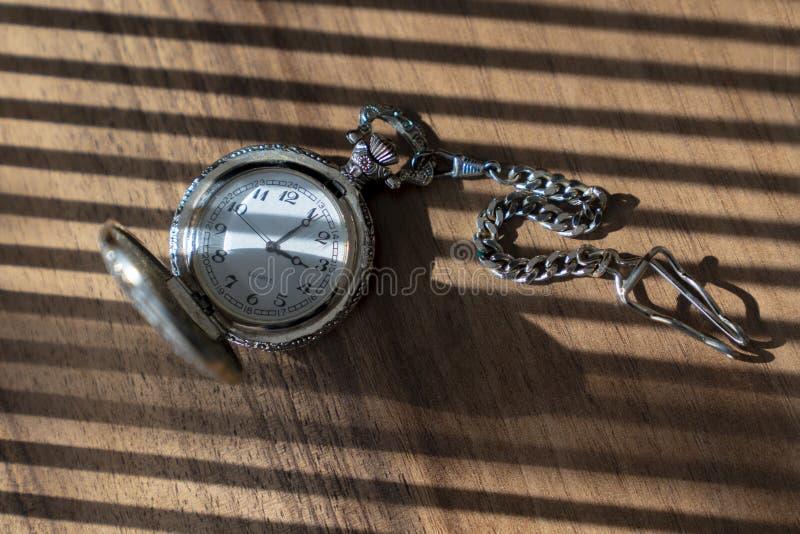 Rocznika kieszeniowy zegarek z cieniem na drewnianym tle pod promieniem światło fotografia stock