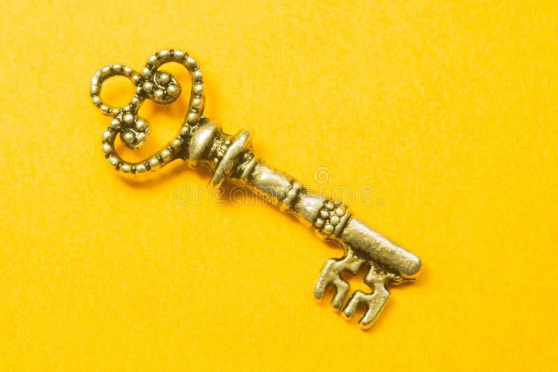 Rocznika klucz odizolowywający na żółtym tle obraz stock