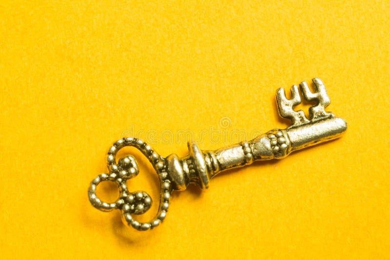 Rocznika klucz odizolowywający na żółtym tle fotografia stock