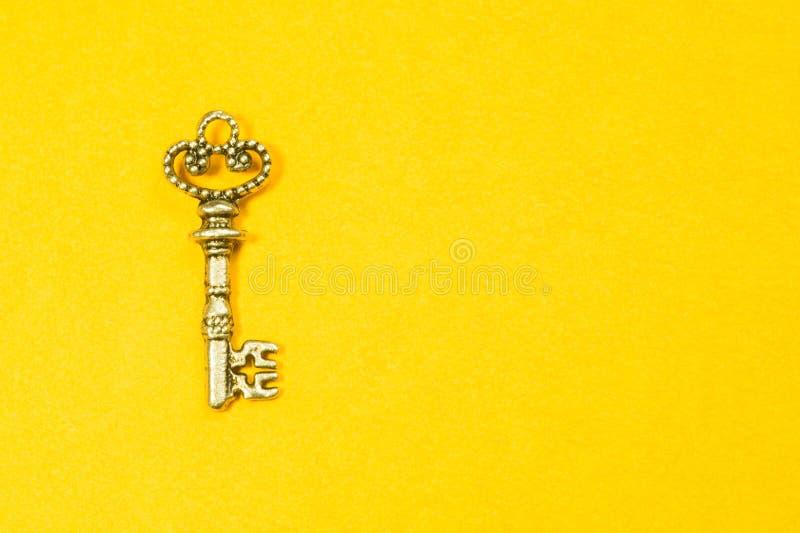 Rocznika klucz odizolowywający na żółtym tle zdjęcie stock