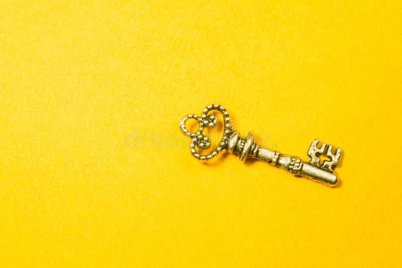 Rocznika klucz odizolowywający na żółtym tle zdjęcia stock
