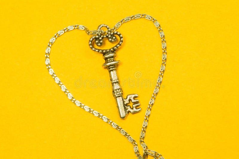 Rocznika klucz z srebro łańcuchem odizolowywającym na żółtym tle fotografia royalty free