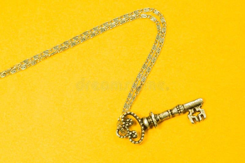 Rocznika klucz z srebro łańcuchem odizolowywającym na żółtym tle obrazy stock