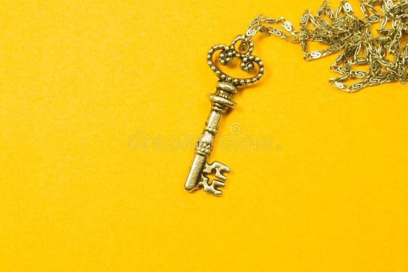 Rocznika klucz z srebro łańcuchem odizolowywającym na żółtym tle obraz stock