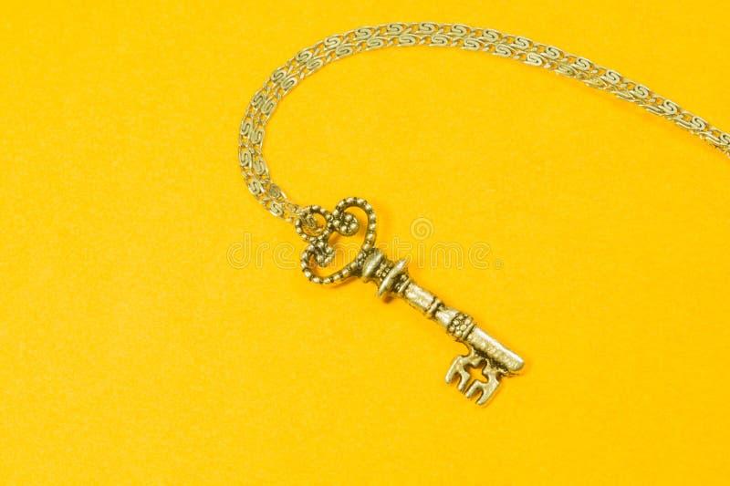 Rocznika klucz z srebro łańcuchem odizolowywającym na żółtym tle zdjęcia stock