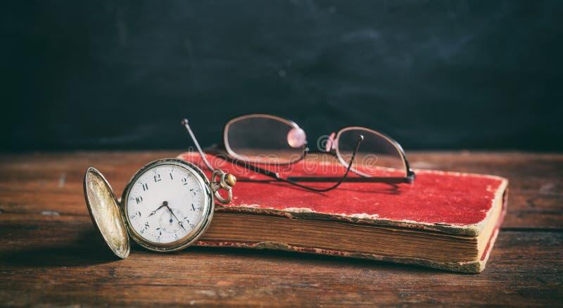 Rocznika książkowy i kieszeniowy zegarek na ciemnym tle obrazy royalty free