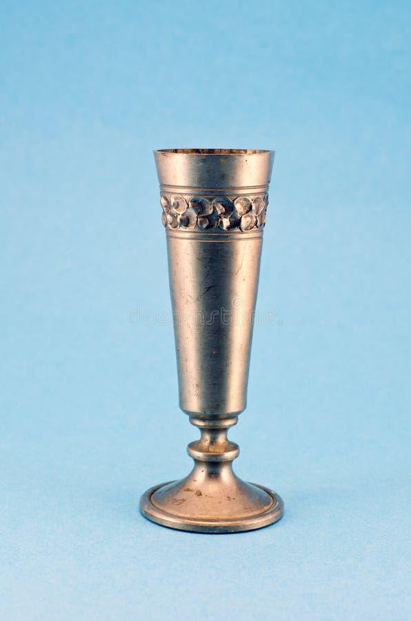 Rocznika metalu czara ornamentacyjna filiżanka na błękitnym tle zdjęcie stock