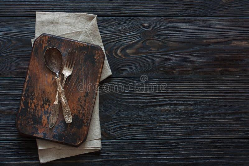 Rocznika metalu rozwidlenie na drewnianym ciemnym tle i łyżka zdjęcie stock
