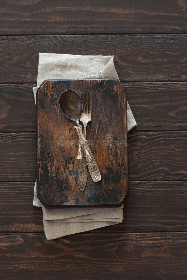 Rocznika metalu rozwidlenie na drewnianym ciemnym tle i łyżka zdjęcia stock