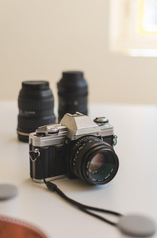 Rocznika 35mm analogu kamera otaczająca z obiektywami i filmem na stole fotografia stock