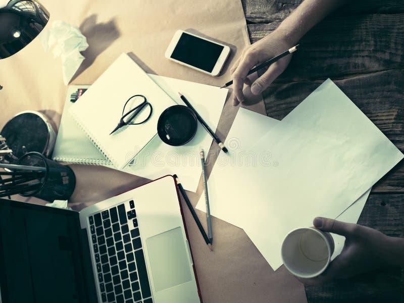 Rocznika modnisia drewnianego desktop boczny widok, samiec wręcza z filiżanką i trzymać ołówek fotografia royalty free