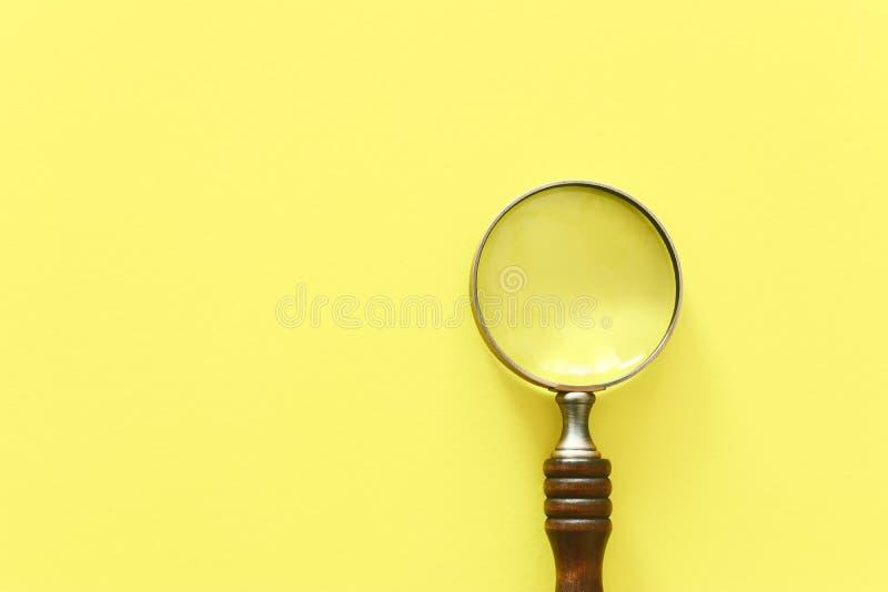 Rocznika powiększać - szkło z drewnianą rękojeścią nad żółtym tłem Odg?rny widok, mieszkanie nieatutowy obrazy royalty free