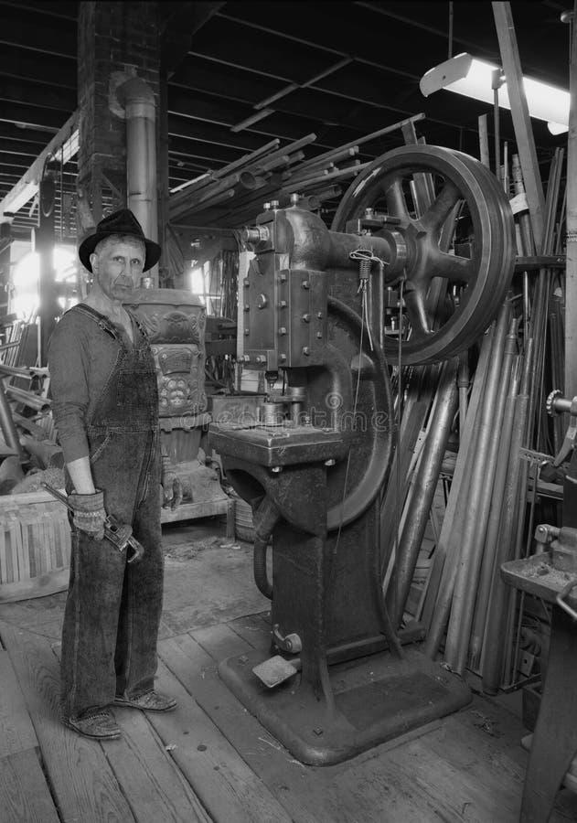 Rocznika Przemysłowy pracownik fabryczny, Fabrykuje Sklepowej podłoga zdjęcie stock