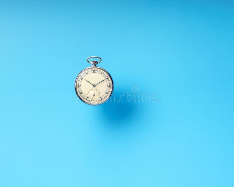 Rocznika round machinalny kieszeniowy zegarek na błękitnym tle fotografia stock