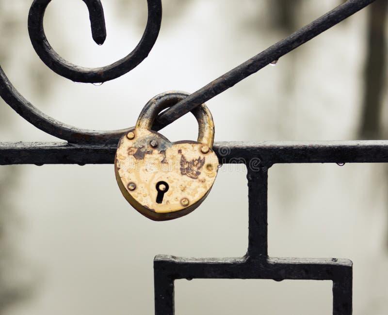 Rocznika serce kształtował kłódkę na ogrodzeniu w deszczowym dniu obraz royalty free