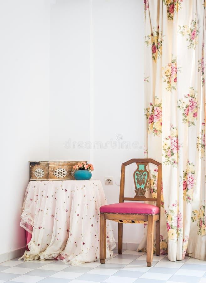 Rocznika stylowy wnętrze z stołem, rzeźbiącym krzesłem i kwiecistą zasłoną, obraz royalty free