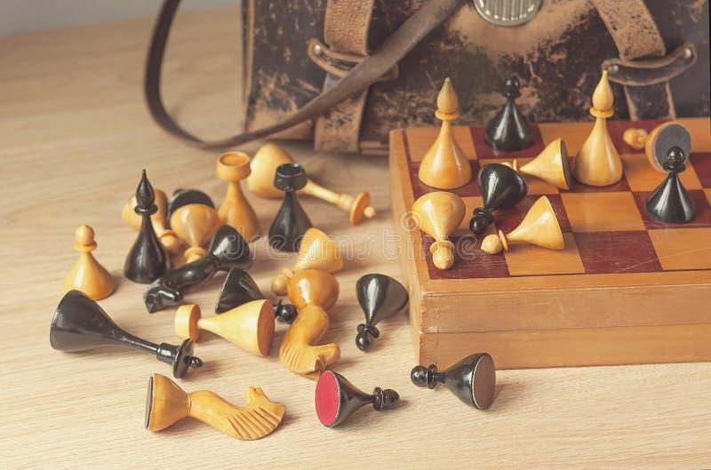 Rocznika szachy i stara rzemienna torba na drewnianej powierzchni obraz stock