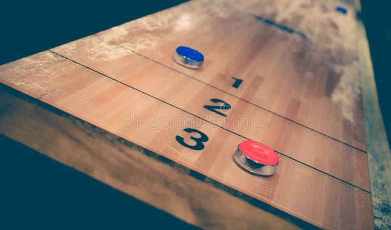 Rocznika tasowania gra planszowa z czerwonym i błękitnym dyskiem na drewnianym tasowanie stole obrazy stock