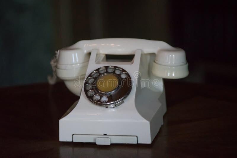 Rocznika telefonu światła beż z dialerem na ciemnym tle obrazy royalty free