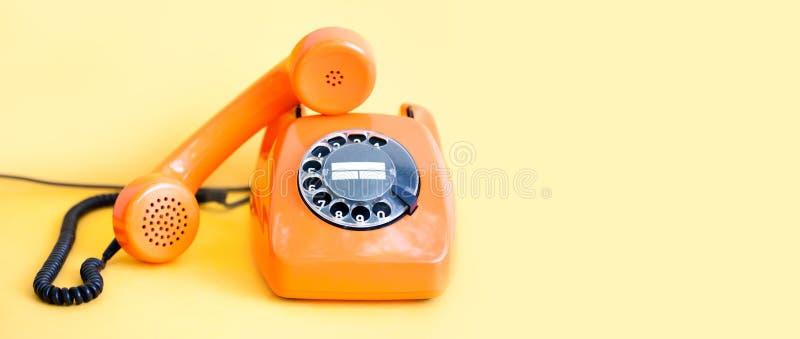 Rocznika telefonu handset ruchliwie odbiorca na żółtym tle Retro stylowego pomarańcze telefonu centrum telefonicznego komunikacyj zdjęcie royalty free