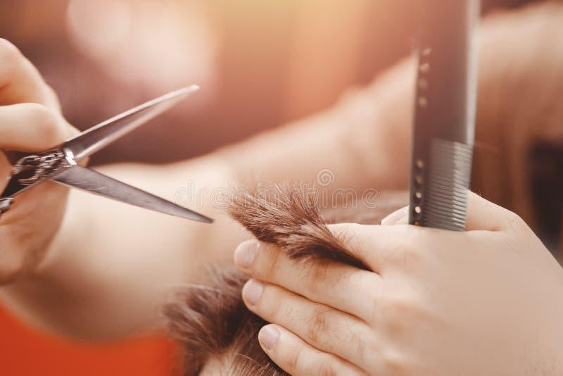 Rocznika tonowanie, mistrzowski fryzjer męski robi włosy obsługiwać modnisia obrazy royalty free