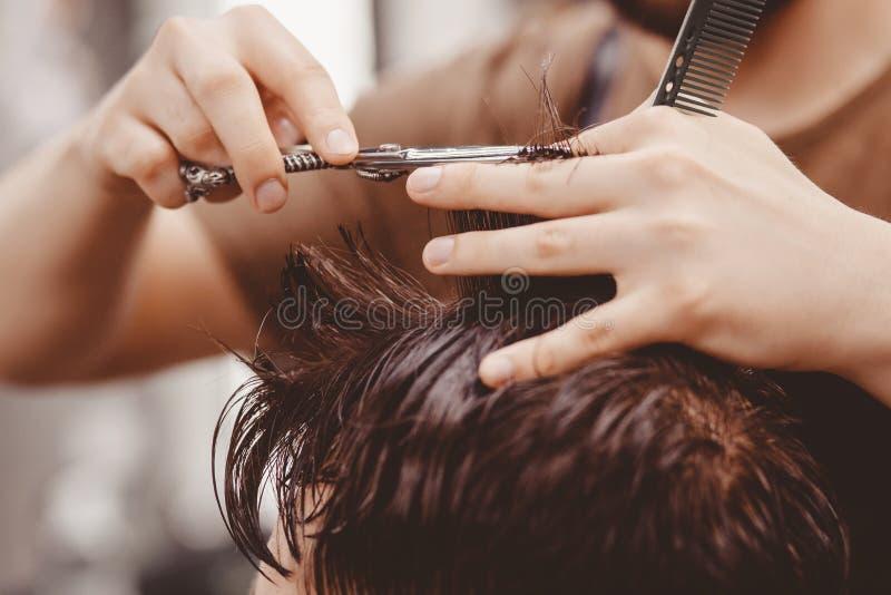 Rocznika tonowanie, mistrzowski fryzjer męski robi włosy obsługiwać modnisia zdjęcia royalty free