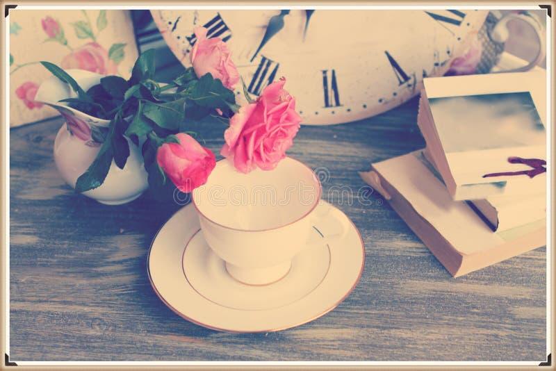 Rocznika wciąż życie z różami filiżanka i książki fotografia royalty free