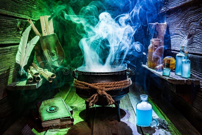 Rocznika witcher kocioł z magicznymi napojami miłosnymi i książkami dla Halloween zdjęcia stock
