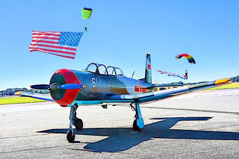 Rocznika wojskowego samolot siedzi w przodzie gdy parachutists lądują w polu za nim zdjęcia stock