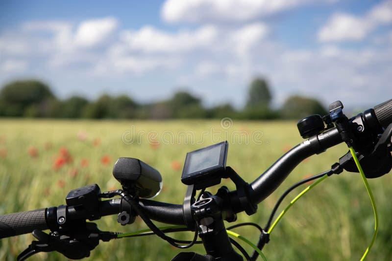 Roda da bicicleta com dispositivos da navegação no fundo de um campo do centeio de mola com papoilas vermelhas Na distância, há imagens de stock