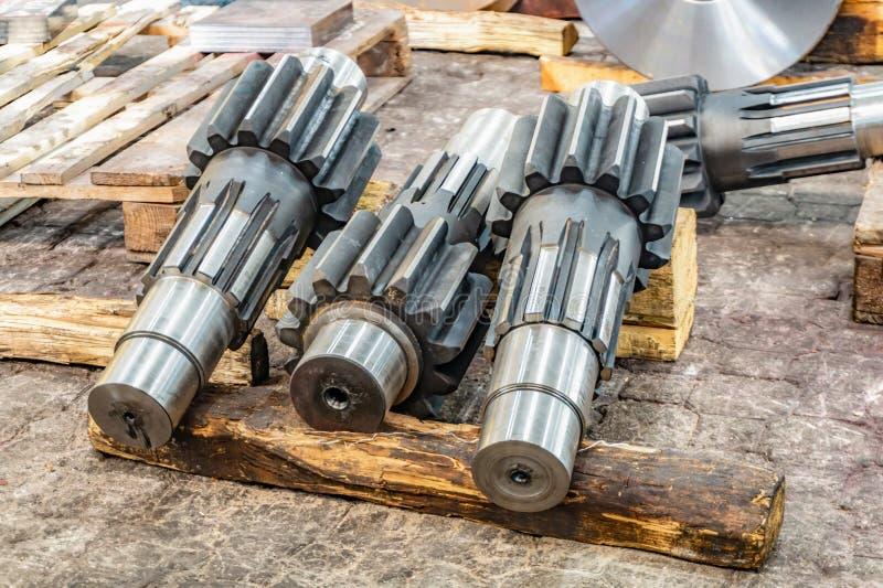 Roda da engrenagem eixo nova em um armazém, em uma cremalheira de madeira após o gerencio e o processamento de trituração, pronto fotografia de stock
