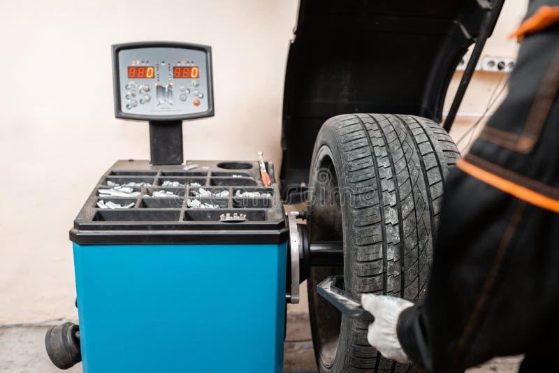 Roda de equil?brio excelente em zero O t?cnico gerencie uma roda de carro A ferramenta para o reparo - conduza pesos e quelas peq fotografia de stock