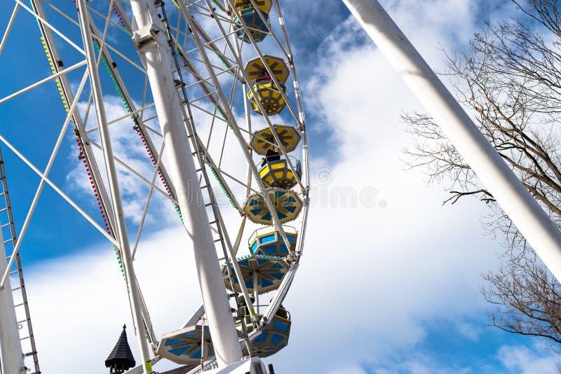 Roda de Ferris com gôndola coloridas em um funfair, contra um céu azul bonito com nuvens brancas fotos de stock