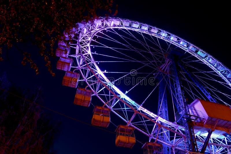 Roda de Ferris com iluminação da cor contra um céu azul da noite imagem de stock