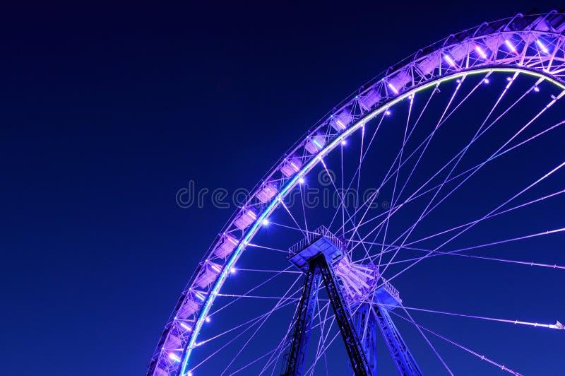 Roda de Ferris com iluminação roxa contra a obscuridade - azul nigh fotografia de stock