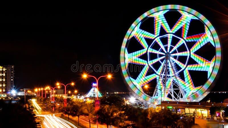 A roda de ferris conhecida como MOA Eye, é iluminada na noite tomada usando uma velocidade do obturador lenta in camera MOA Eye F fotos de stock
