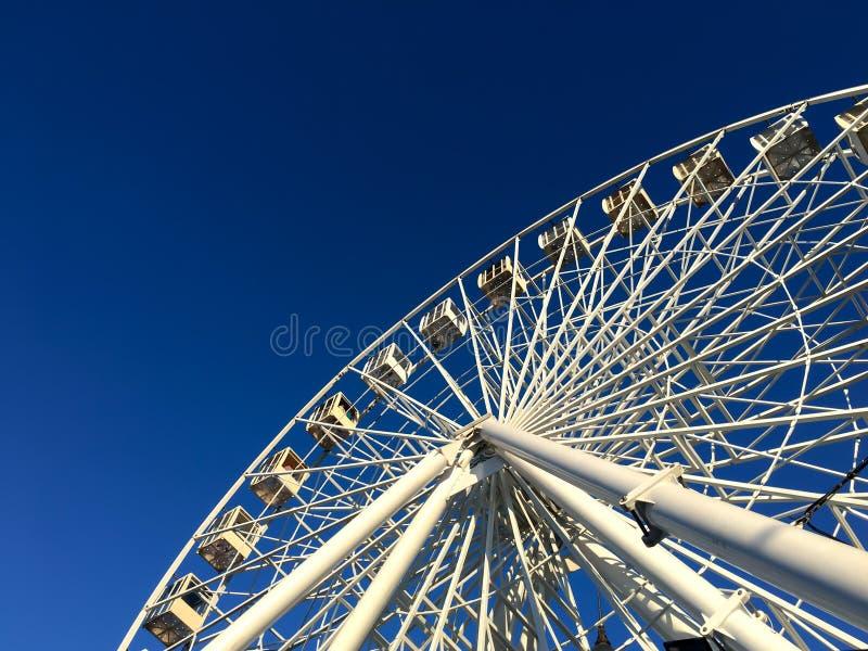 Roda de ferris gigante contra um céu azul em um estilo minimalista, formas geométricas simples imagens de stock royalty free