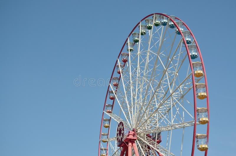 Roda de ferris multicolour grande e moderna no fundo limpo do céu azul imagem de stock
