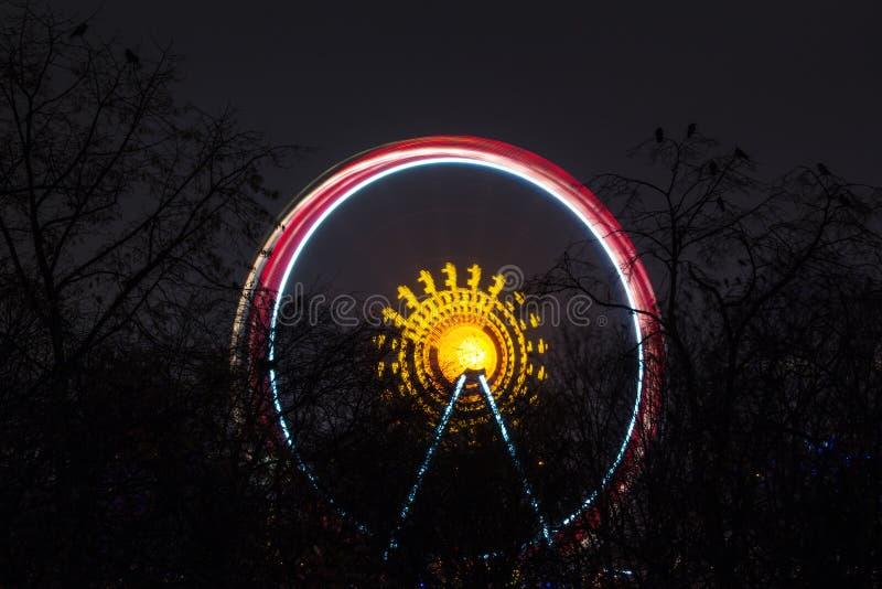 Roda de Ferris que gira na noite imagem de stock