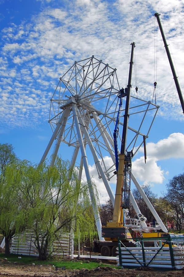 Roda de Ferris sob a construção imagem de stock royalty free