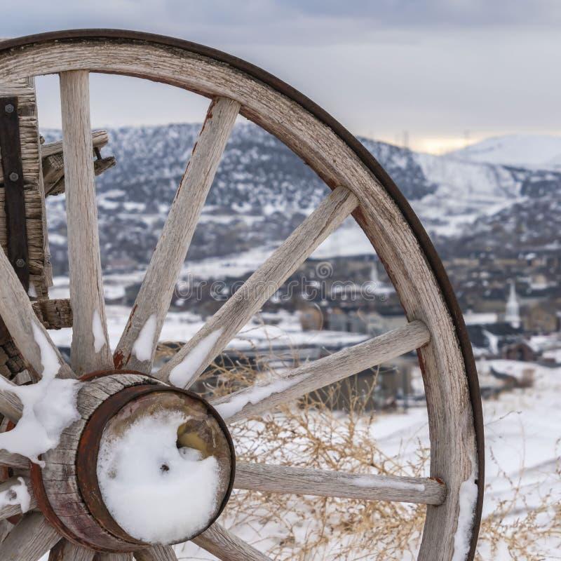 Roda de madeira do quadrado com metal oxidado de um carro antiquado visto no inverno fotos de stock royalty free