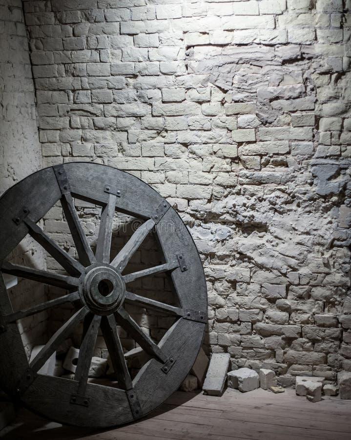 Roda de madeira perto de uma parede de pedra foto de stock royalty free