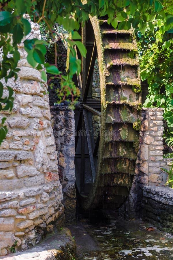 Roda de madeira de um moinho de água antigo em jardins botânicos de Balchik e em palácio da rainha romena Marie em Bulgária imagens de stock