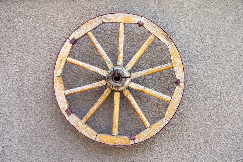 Roda de madeira velha do cavalo-carro na parede imagem de stock royalty free