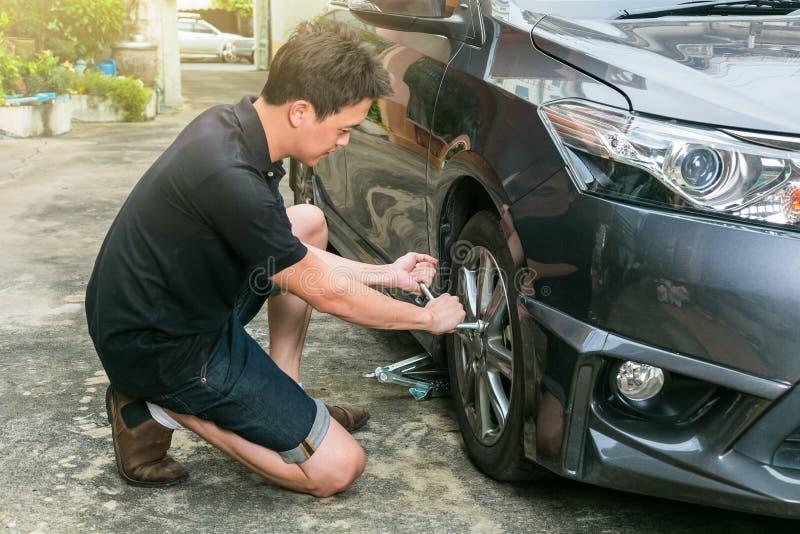 Roda de mudança do homem novo de seu carro na estrada foto de stock royalty free