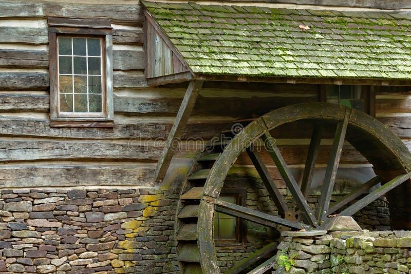 Roda de pá de madeira da água e pedras musgosos no lado de um velho foto de stock