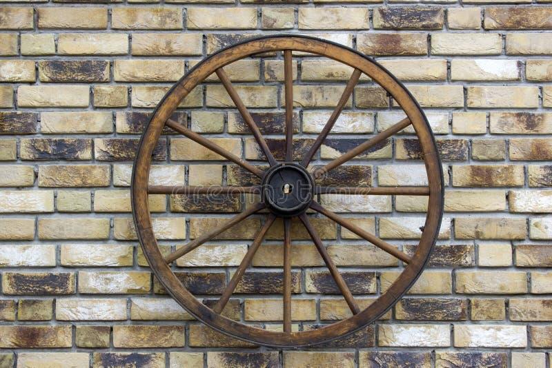 Roda de vagão rural em uma parede de tijolo imagem de stock