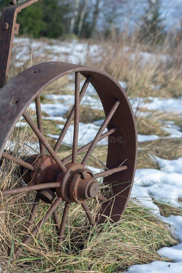 Roda do ferro do vintage na grama seca e no fim da neve acima fotos de stock