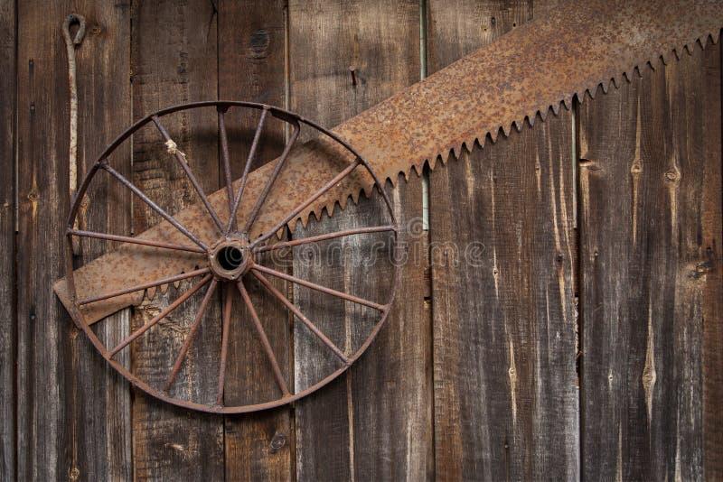 A roda oxidada do metal pendura na parede das placas idosas imagem de stock royalty free