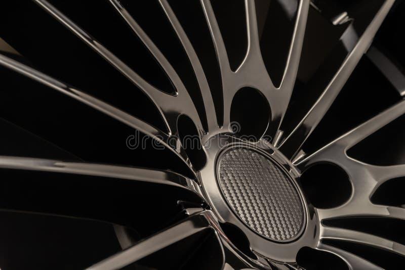 Roda preta luxuosa nova da liga, desportiva com raios finos, close-up no fundo preto foto de stock royalty free